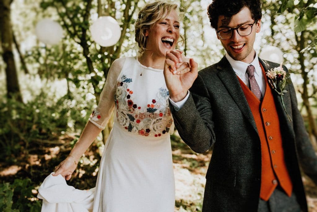 bride and groom walking through forest on wedding day laughing and smiling