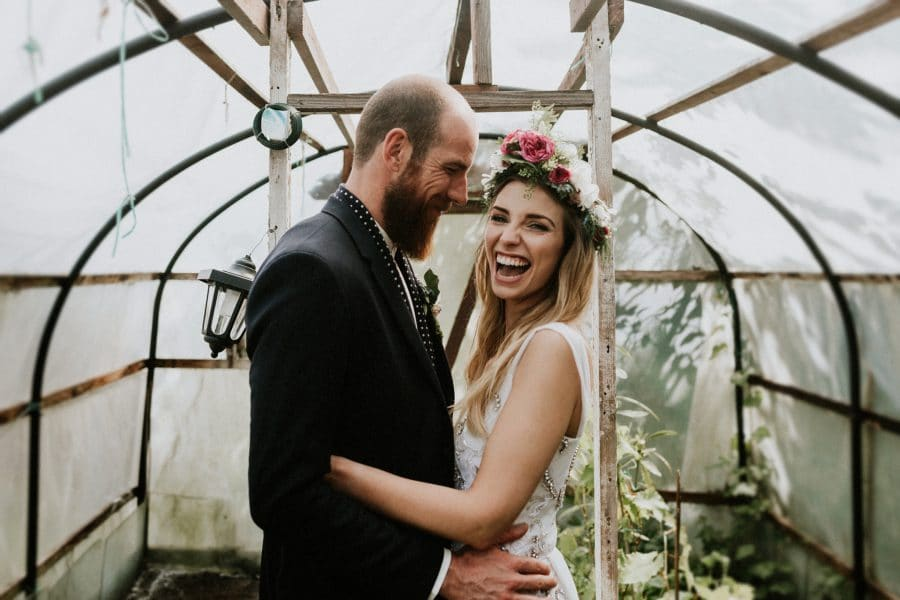 bride hugging groom and looking into the camera laughing on allotment