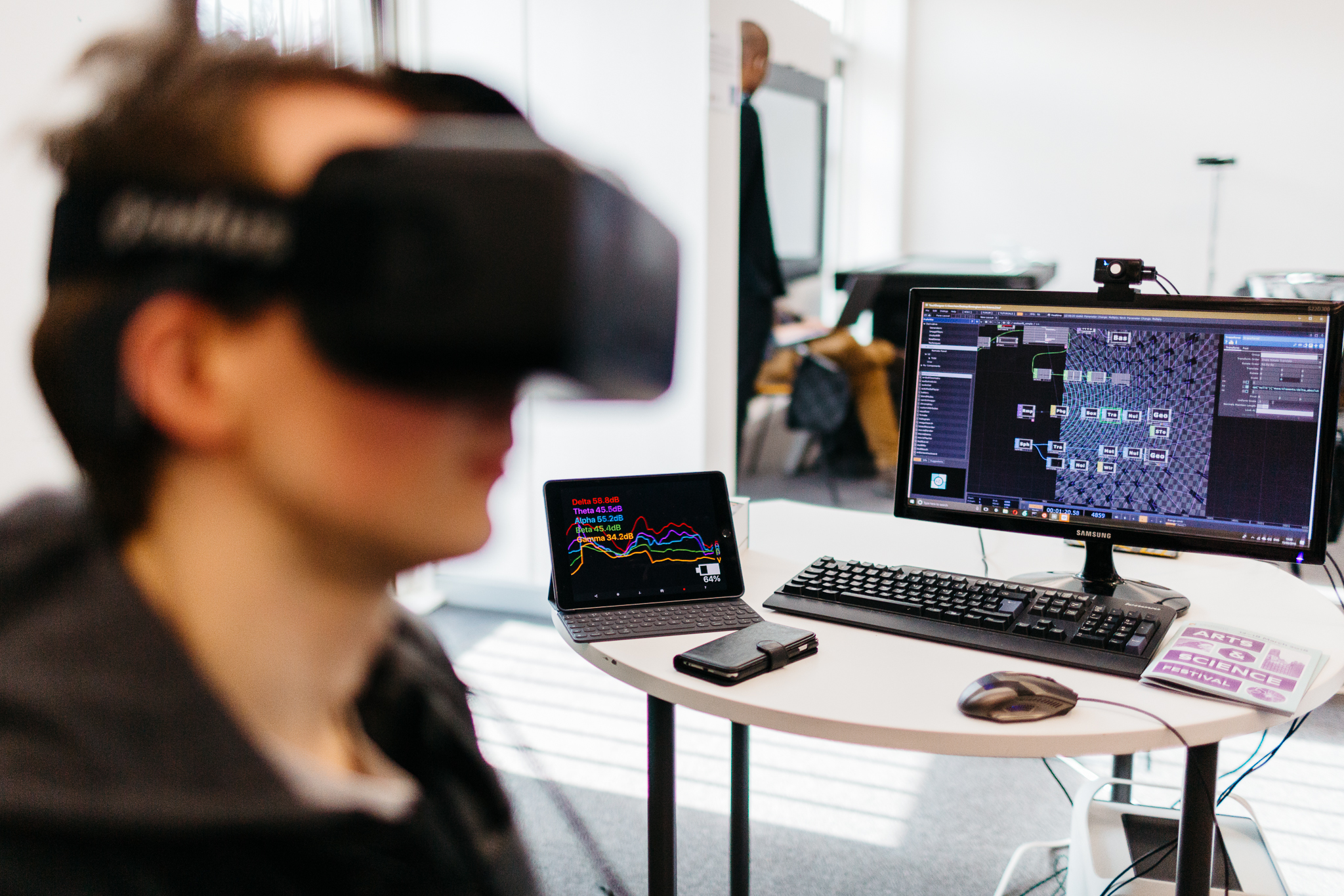 woman wearing VR goggles infront of a computer