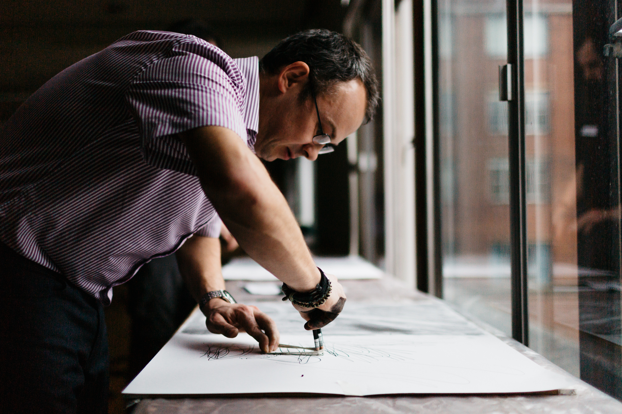 man drawing infront of window