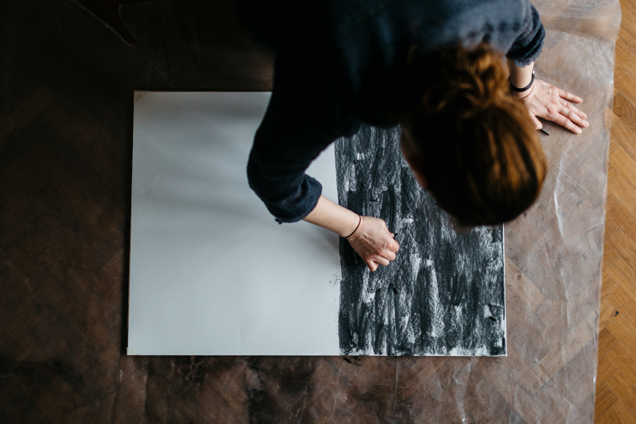 woman drawing with charcoal on floor during a workshop at festival