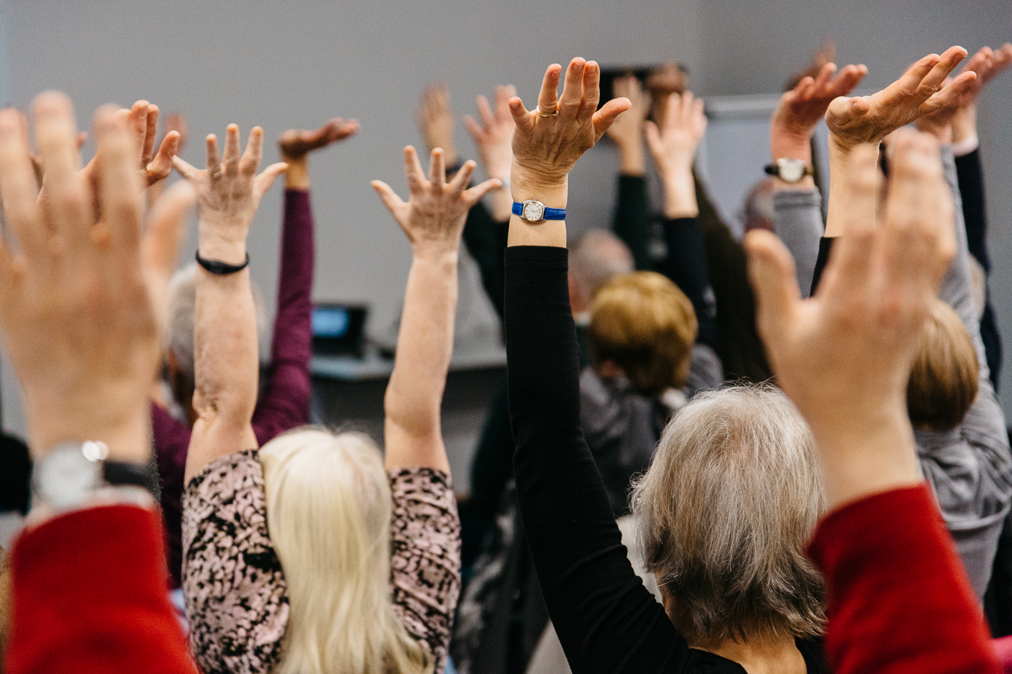 hands in the air at a chair workout class