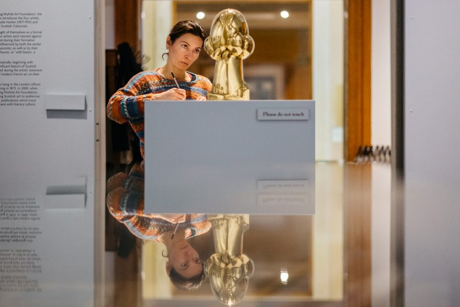 woman looking at object in museum