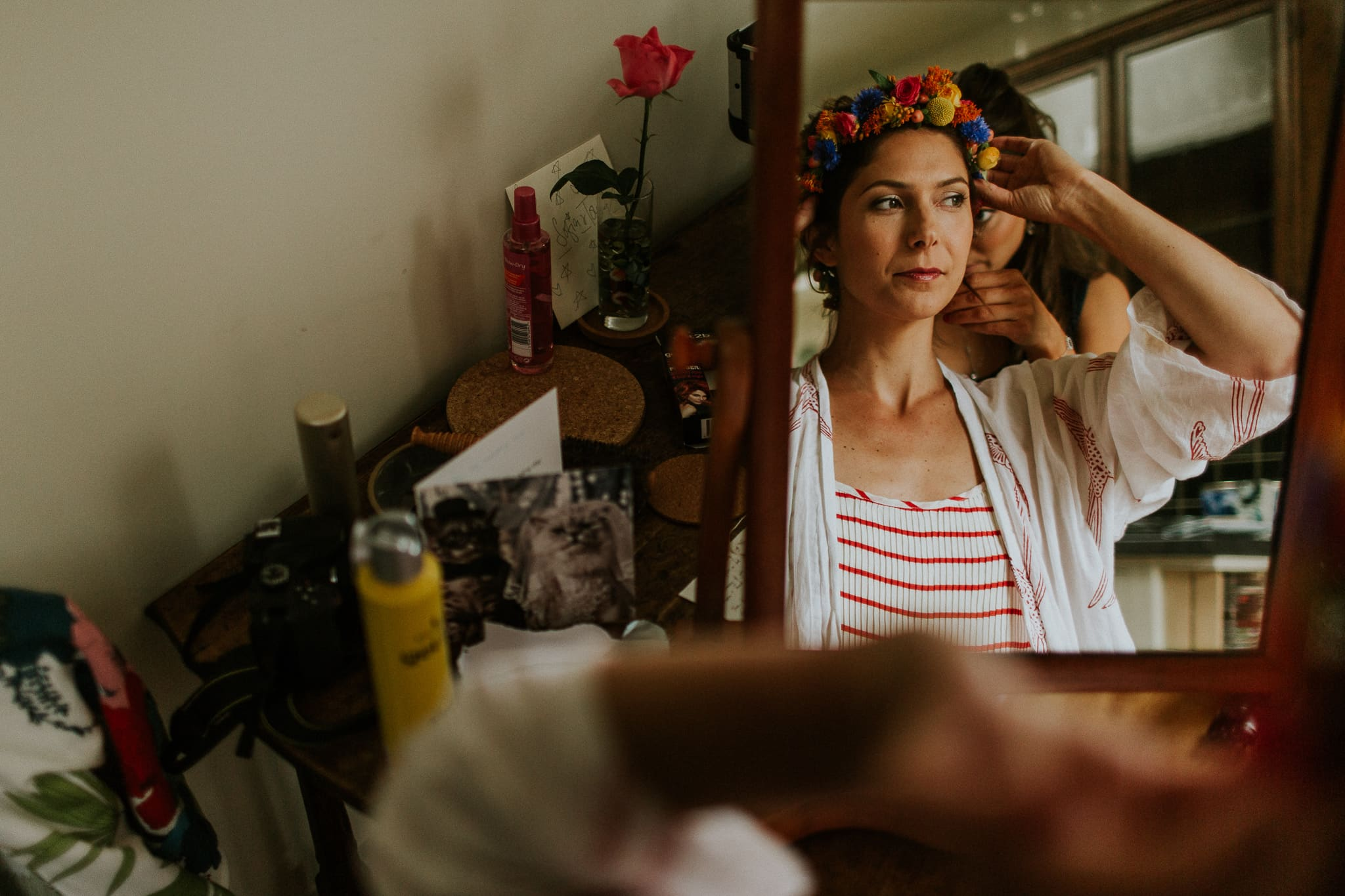 bride adjusting her hair piece in mirror