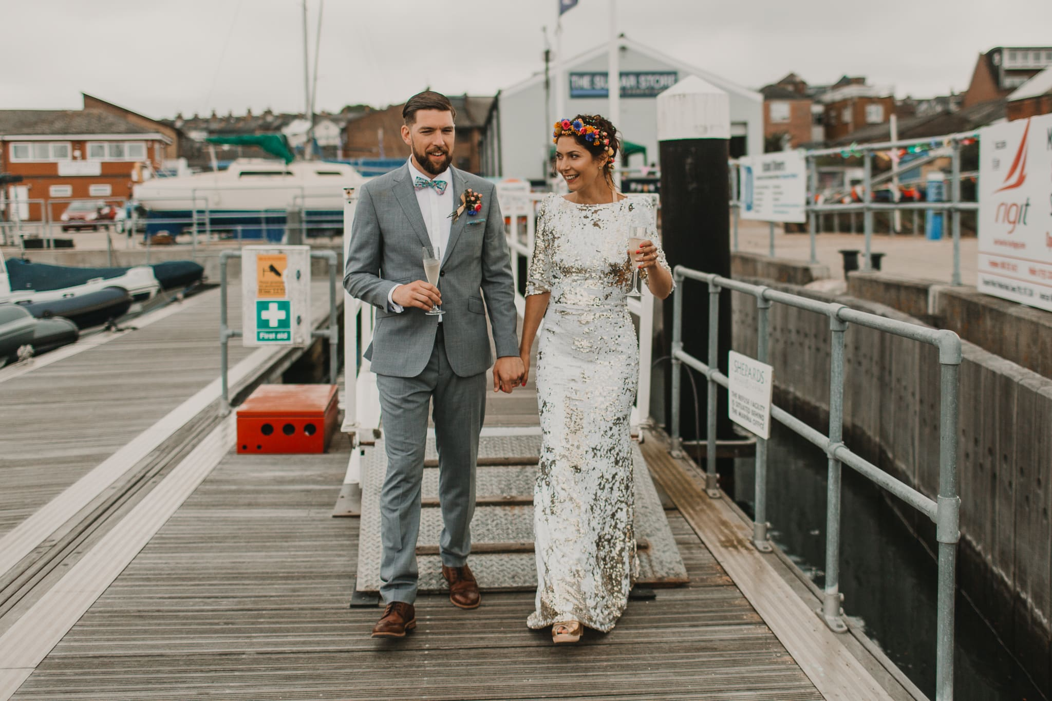 bride and groom walking on pier laughing and drinking