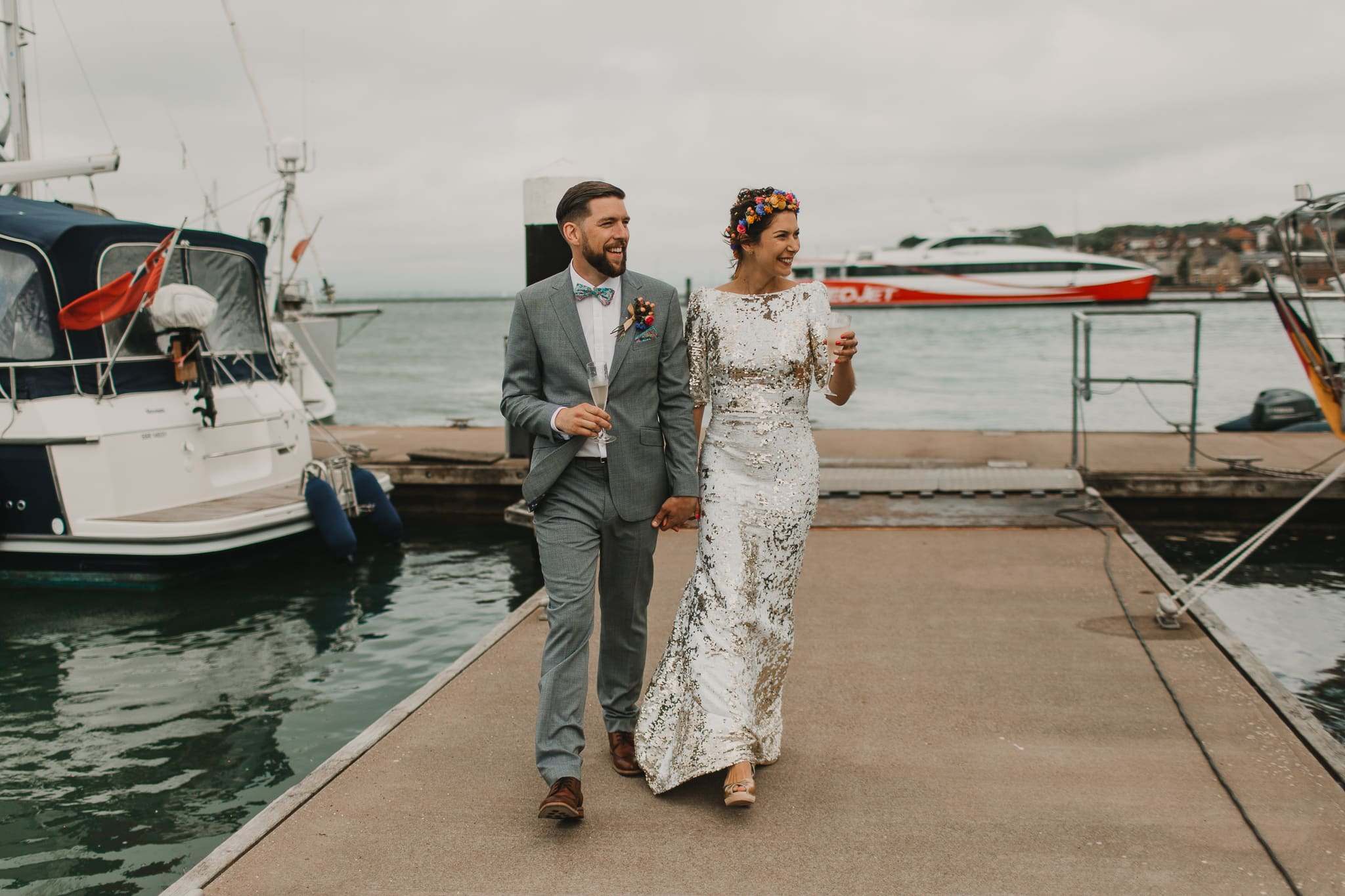 bride and groom walking on harbour smiling
