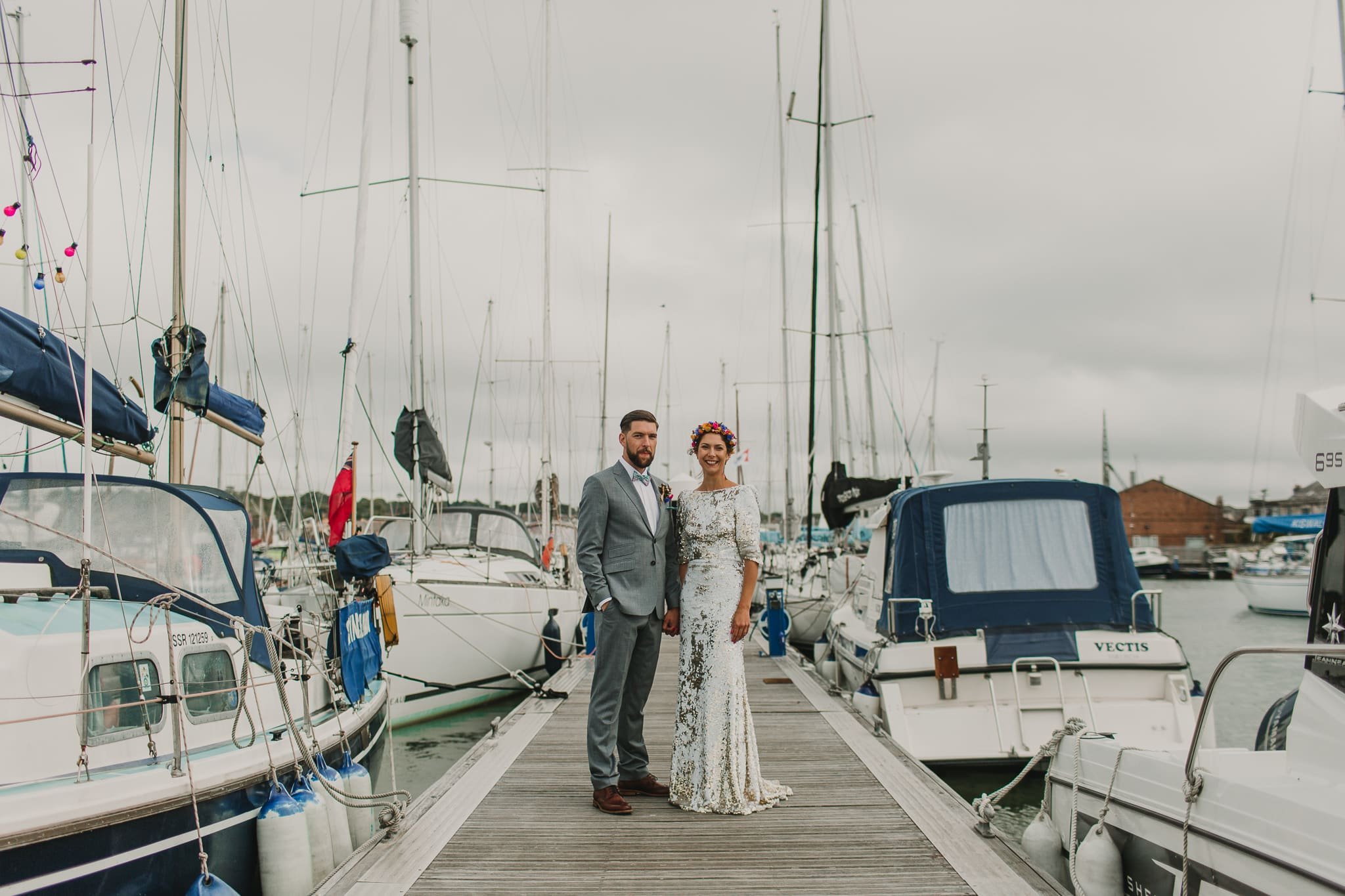 bride and groom standing on pier infront of boats