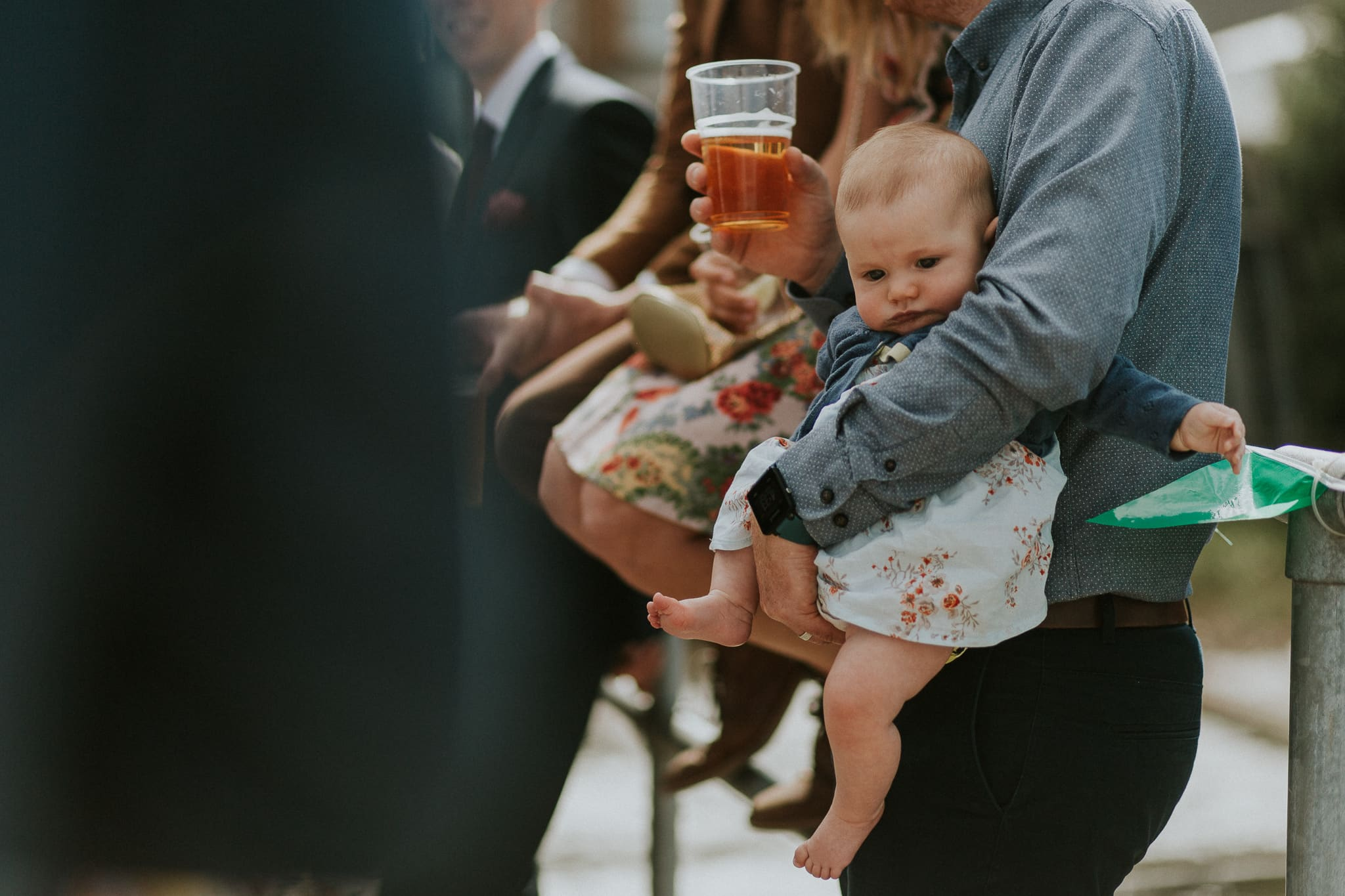 Wedding guest holding a baby during speeches