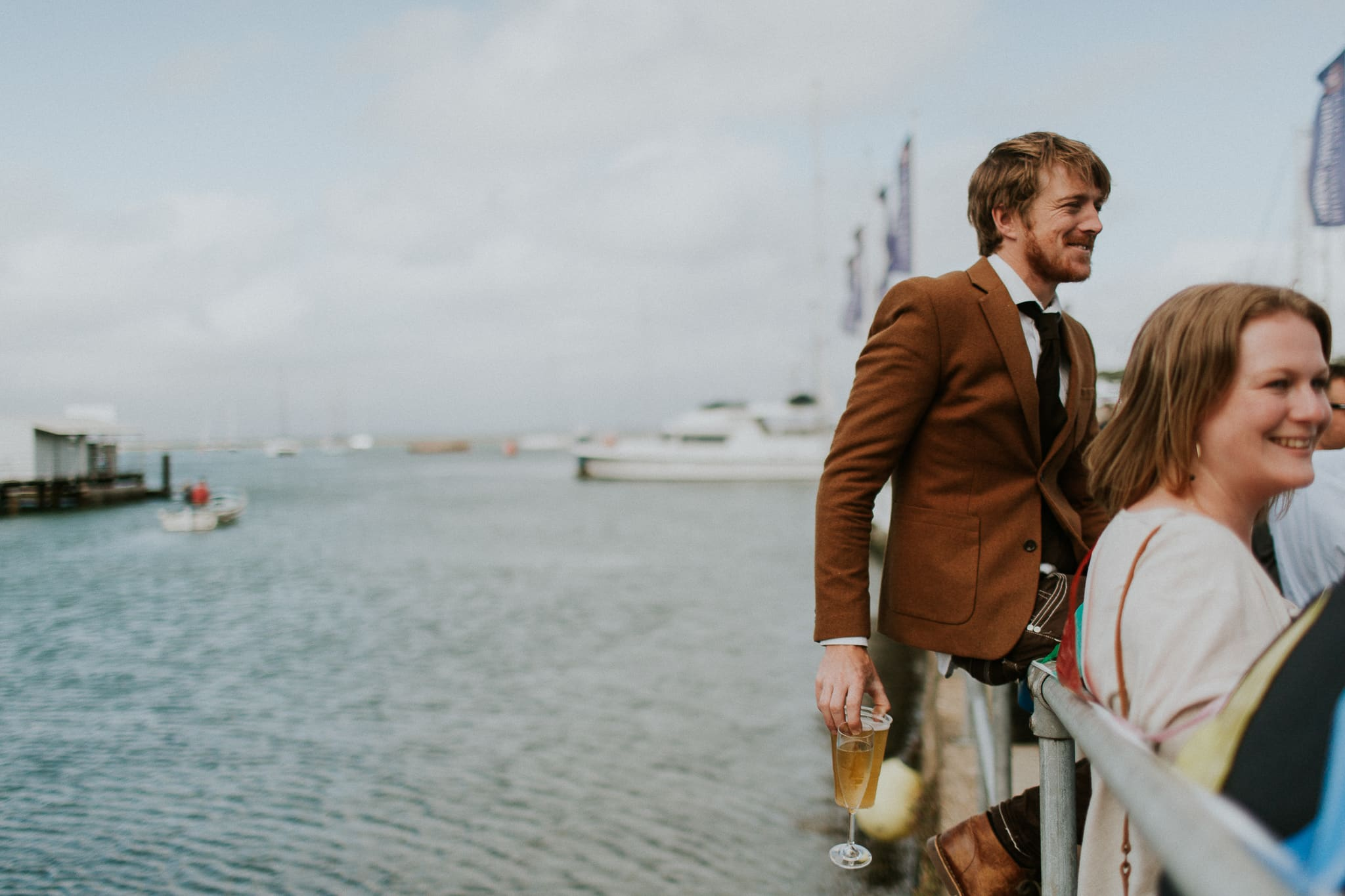wedding guest sitting on pier holding a beer