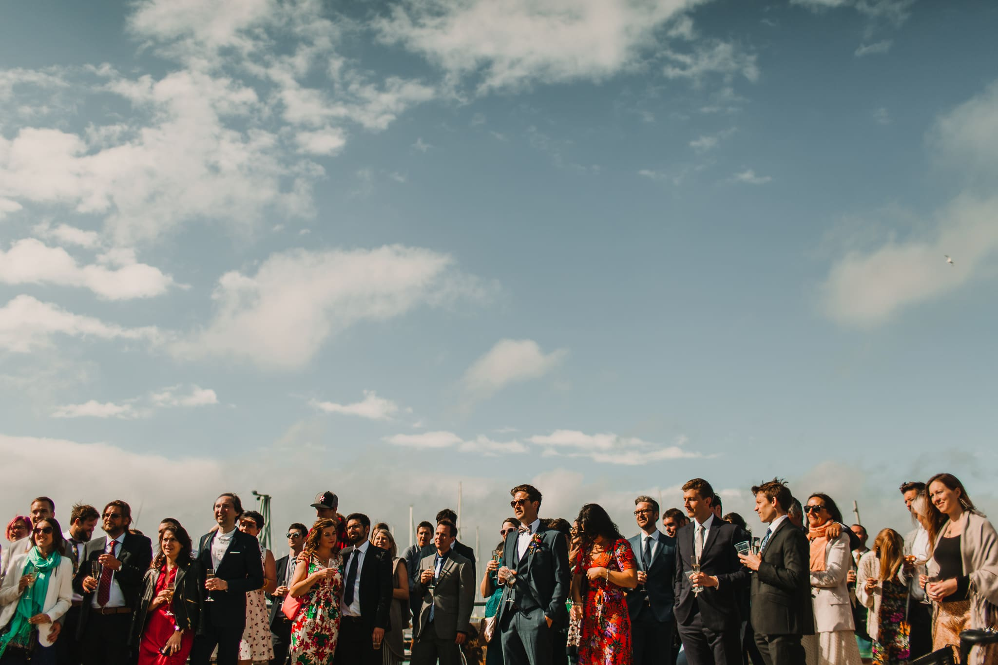wedding guests standing on pier listening to speeches