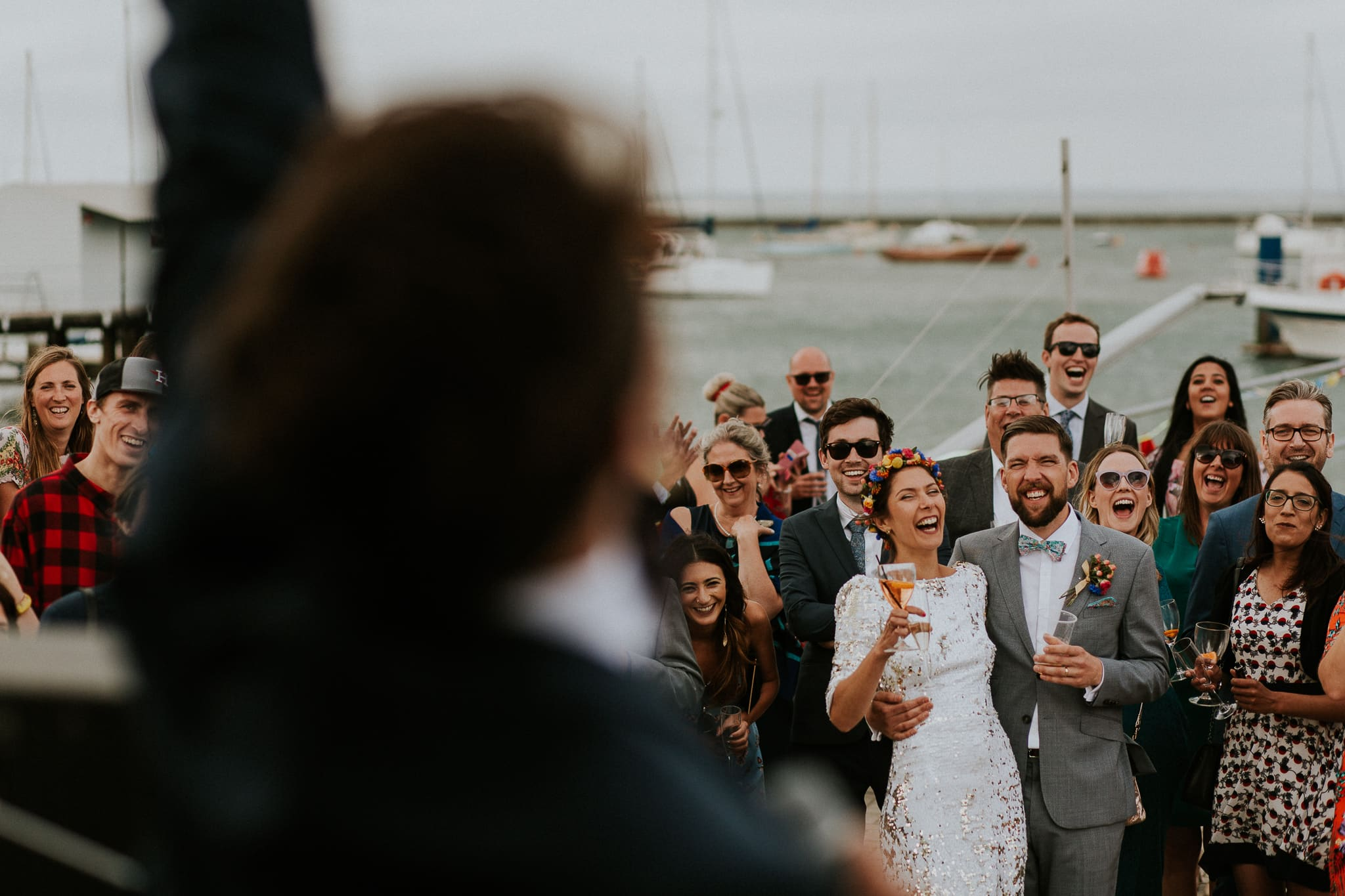 bride and groom laughing at best man's speech on a pier