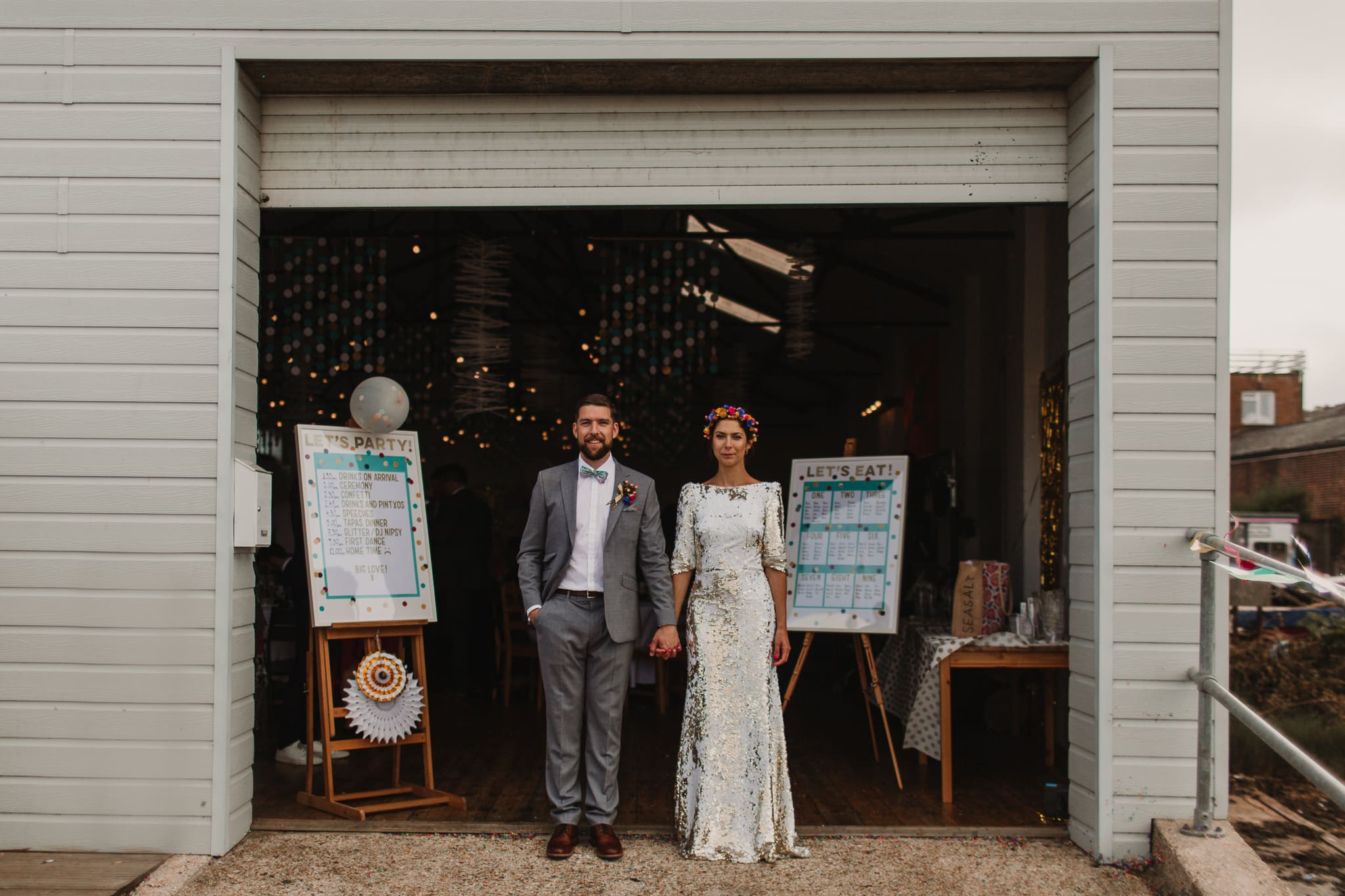 bride and groom standing infront of boathouse on harbour