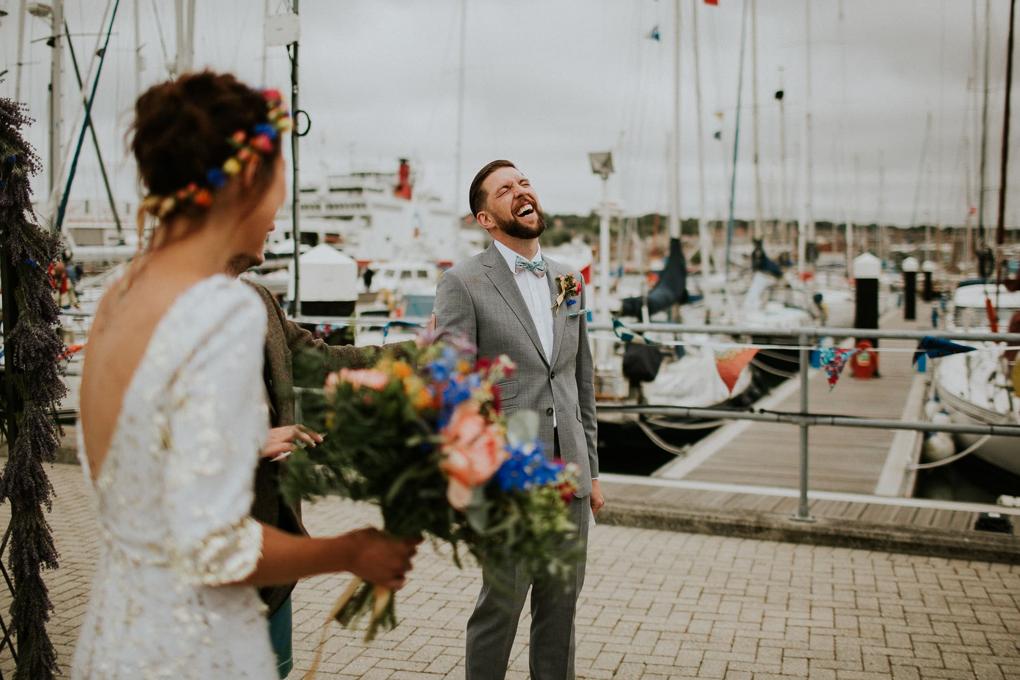 groom laughing during ceremony on a pier