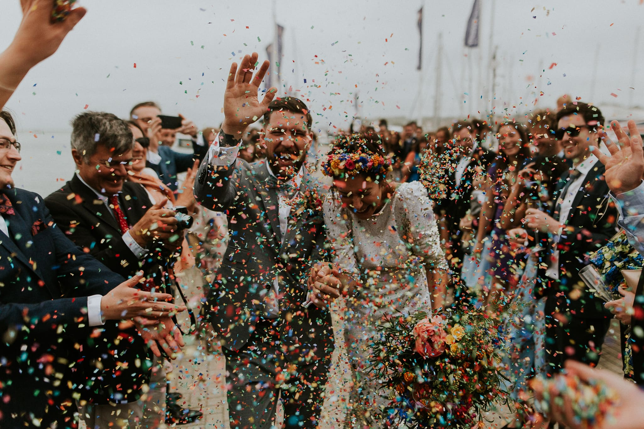 bride and groom running through a confetti throw