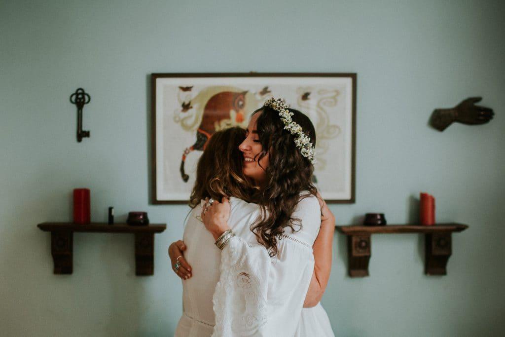 bride hugging mother in bedroom
