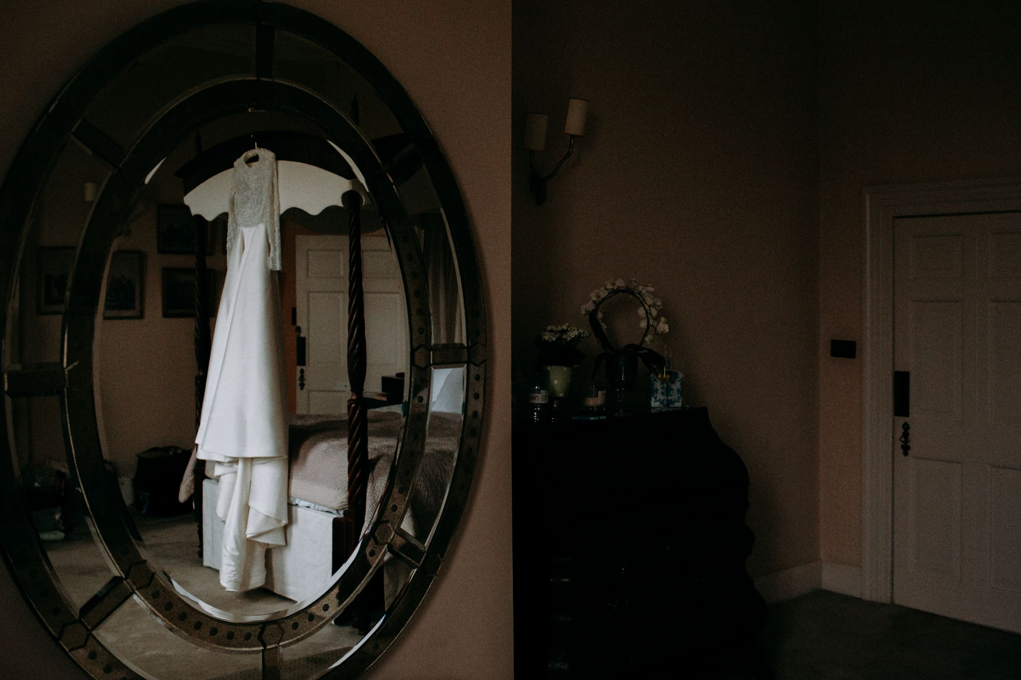 wedding dress hanging infront of a mirror in a country home