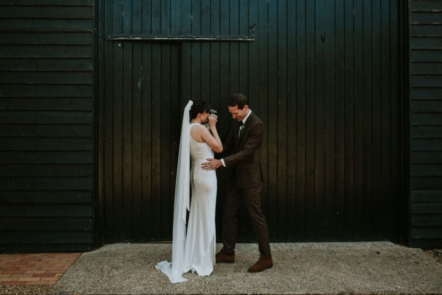 bride and groom talking in front of large blue door